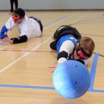 A goalball heads straight for the camera as a goalball player reaches for it