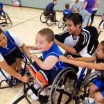 a group of smiling youth athletes surround a teammate and pat him on the back