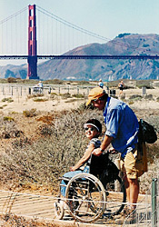 An able-bodied man walks with a woman in a wheelchair with the Golden Gate Bridge in the background