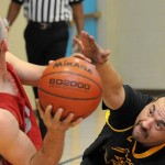 An adult wheelchair basketball player reaches forward to try and block another player's shot