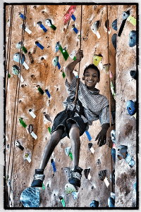 A Junior Adventurer enjoys an indoor climbing wall