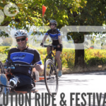 a group of cyclists ride past trees and vinyards - text: Revolution Ride and Festival