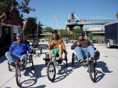 Three vets on adaptive cycles give the thumbs up before a ride