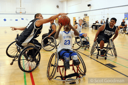 A wheelchair basketball player reaches to block a shot in a game