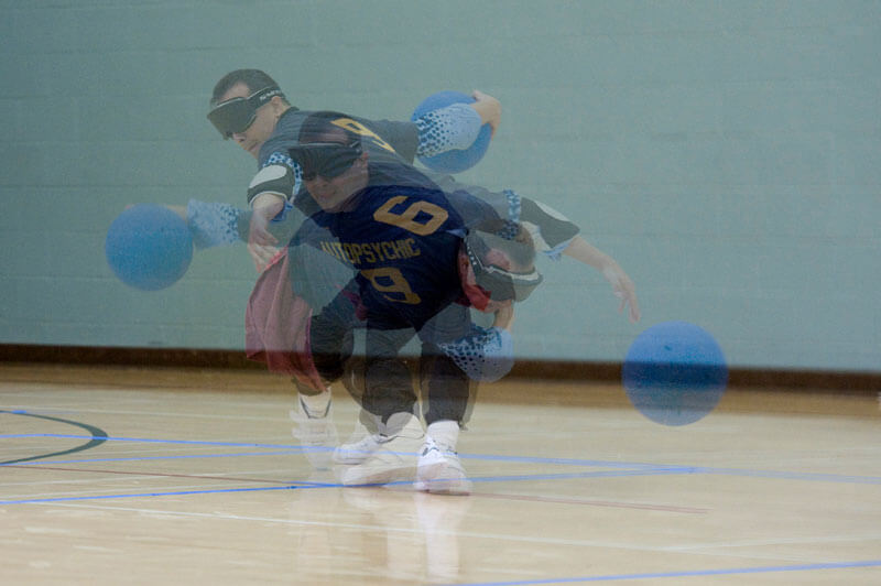 Photo has three exposures of a player throwing a goalball