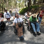 Three people in wheelchairs with able-bodied volunteers behind share a laugh on a shady