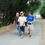 Two hikes with visual impairments are escorted by a sighted guide on a wooded trail