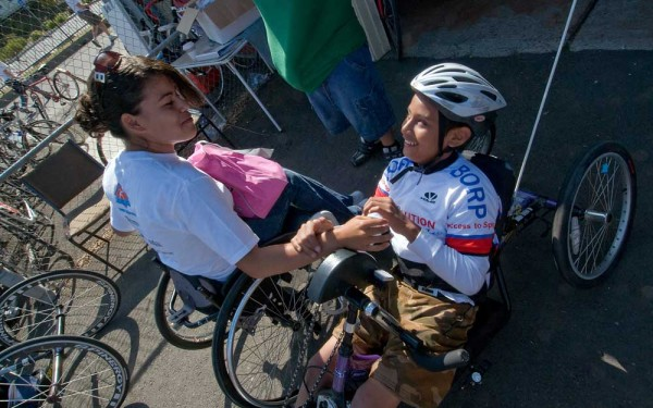 A young handcyclist gets some encouragement from a friend before a ride