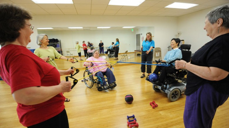 BORP adaptive fitness class with six woman in a circle pulling resistance bands