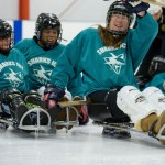 A female sled hockey player waves to the camera with two teammates following