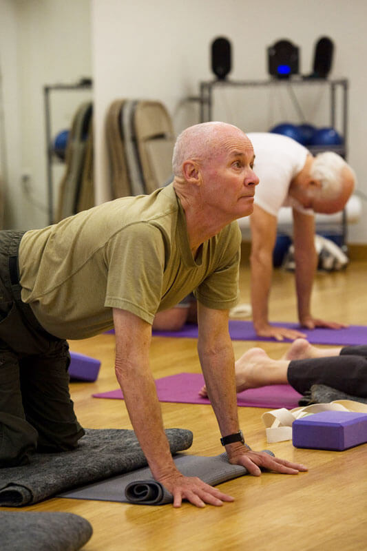"""Two members of a Yoga for Seniors class in the """"cat and cow"""" positions"""