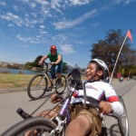 A young adaptive cyclist enjoys a ride with a friend on a conventional bicycle under blue skies