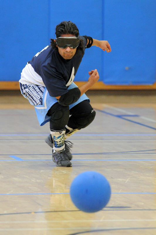 A goalball in the forground a microsecond after leaving the background player's hand