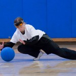 A woman dives to make a defensive stop in a goalball match