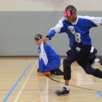 A goalball player about to throw the ball down the floor with a teammate in the background