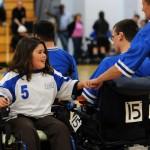 A BORP power soccer player gives a fist bump to an opposing coach