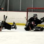 A goalie makes a save while an opposing player looks on