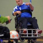 A power scoccer player pops a wheelie during a match
