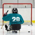 A youth sled hockey player faces the goal at the far end of the ice
