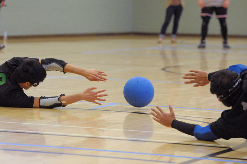 A goalball rolling right between the outstretched hands of two defenders