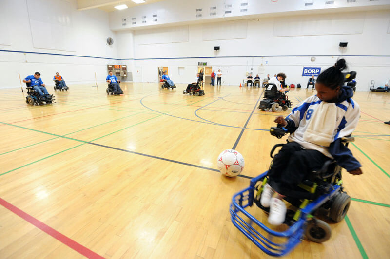 A player prepares to put a ball in play with a view of the whole court during a power soccer match