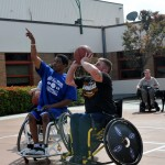A veteran receives insruction from a BORP player on wheelchair basketball