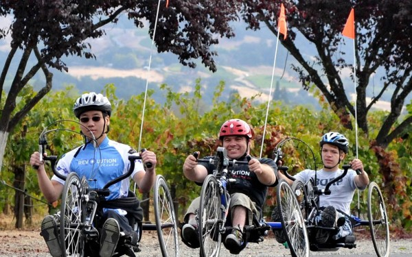 Three handcyclists ride in a row at the 2012 Revolution