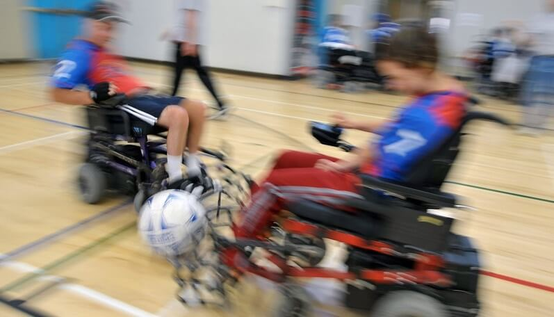 Two power soccer players are a blur of speed as they converge on a soccer ball