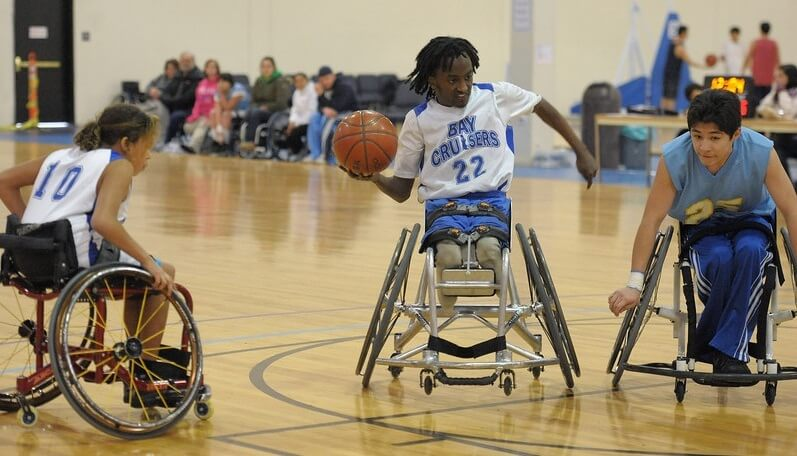 A youth wheelchair basketball player prepares to pass the ball