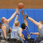 Five players reach for a basketball above them