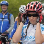 A focused cyclist puts on her sunglasses