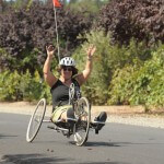 A woman riding an adaptive cycle raises her hands triumphantly