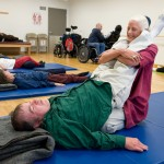 A BORP fitness instructor assists a class participant in an adaptive yoga class