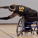 An adult wheelchair basketball player reaches for a ball