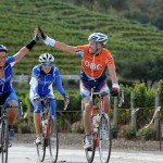 Two cyclists high five while a third looks on