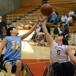 Two youth wheelchair basketball players reach for a basketball in the air above them