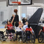 Youth wheelchair basketball players watch a ball pass though the net during a game