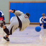 A goalball player follows through after throwing towarsds his oppenents