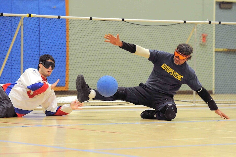 Bill makes a kick block in front of a goalball net
