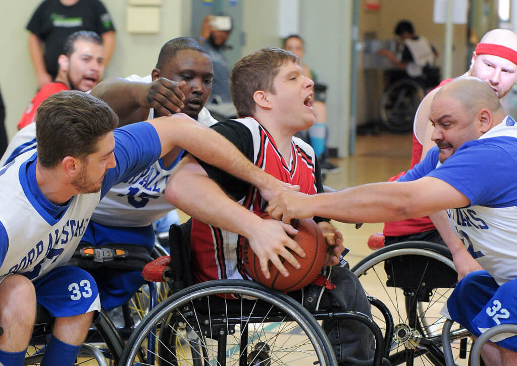 Members of the BORP All Stars wheelchair baseketball team surround an opponent
