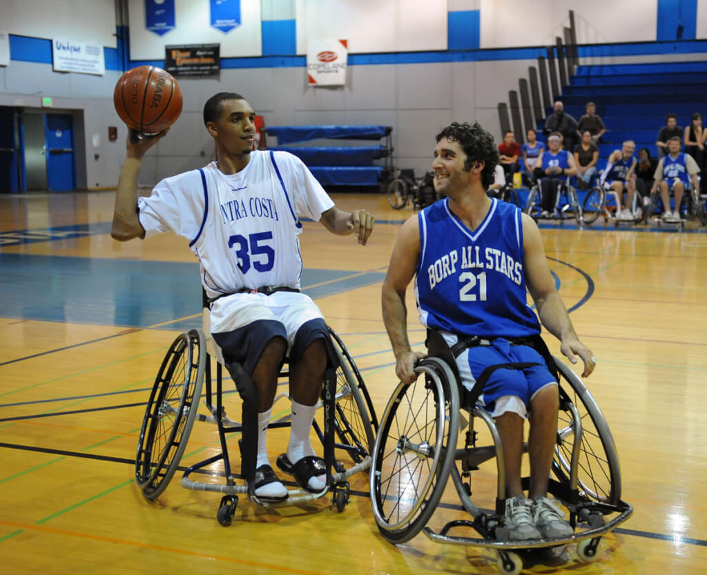 Whhelchair basketball players form BORP and Contra Costa College share a lugh during an exhibition game