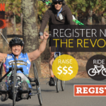 Register Now for the Revolution -- a hand cyclist raises her arms in the air to celebrate during the Rev.
