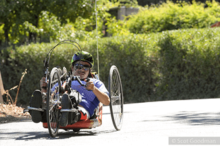 A hand cyclist wearing a 2016 Revolution jersey rides toward the camera