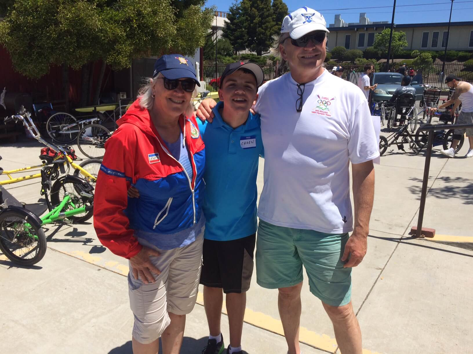 All smiles after learning to row, a young BORP participant poses with two former Olympic rowers, Charles Alterkruse (1980 & 1988 Olympics) and Liz Miles (1984 Olympics).