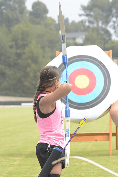 Ella aiming for the target during the archery clinic