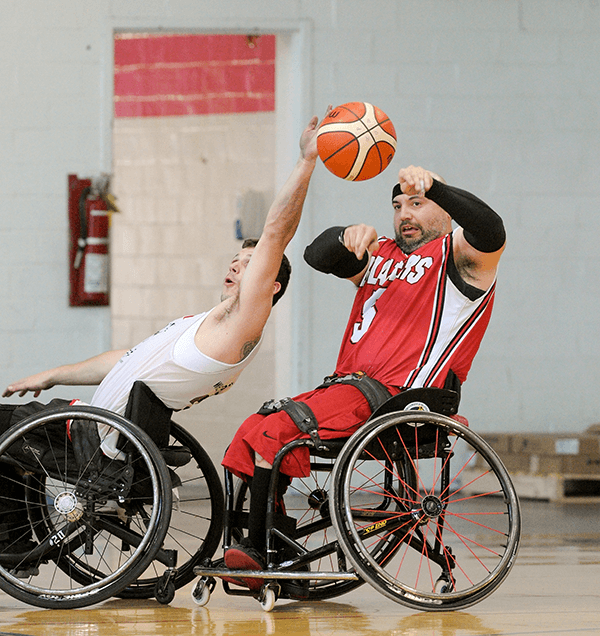 Player attempts to block a pass, wheelchair basketball
