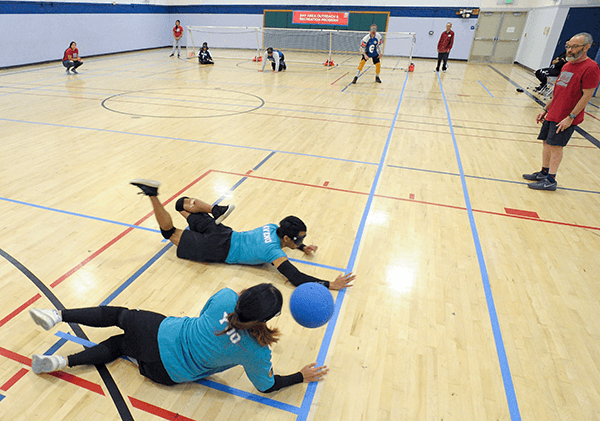 Goalball players diving to defend their goal
