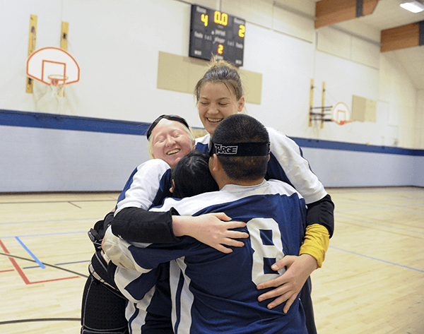 Cal Goalball players embrace, celebrating their win