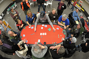 Photo looking down on a red poker table surrounded by players.
