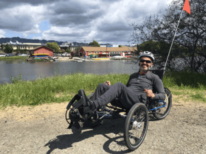 "CNS ""graduate"" Ray Ydoyaga on a recumbent trike near the BORP Cycling Center"